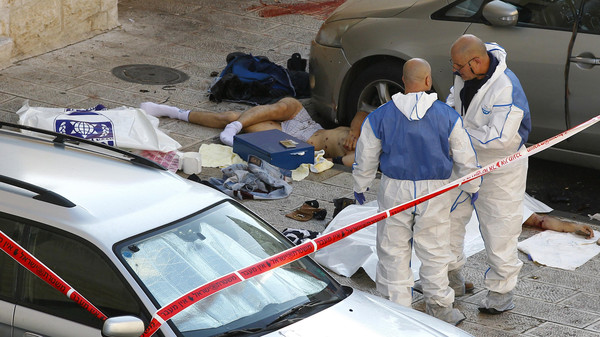 Israeli police crime scene investigators stand near bodies of suspected attackers outside a Jerusalem synagogue