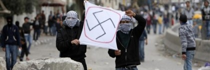 Palestinians hold a sign depicting a swastika during clashes at Qalandiya checkpoint near the West Bank city of Ramallah March 19, 2010. Stone-throwing Palestinians clashed with Israeli security forces in several locations in East Jerusalem and the West Bank amid tensions over Israel's recently announced plan to build houses in East Jerusalem.  REUTERS/Mohamad Torokman (WEST BANK - Tags: POLITICS CIVIL UNREST)