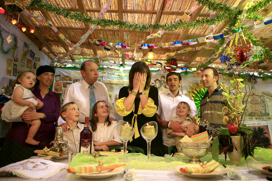 A Jewish family sit inside a Sukkah (temporary dwelling) in the settlement of Neve Daniel. The Sukkah is one of the rituals in the week-long Jewish holiday of Sukkot. Sukkot commemorates the Israelites 40 years of wandering in the desert and a decorated hut or tabernacle is erected outside religious households as a sign of temporary shelter.