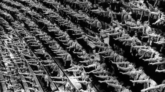 An Associated Press photograph shows some of over 132,000 members of the Hitler youth organisation assembled at the Olympic Stadium in Berlin, where German Chancellor Adolf Hitler and Dr. Joseph Goebbels addressed them, as part of the usual round of May Day festivities and demonstrations in Germany on May 1, 1939. The AP caption notes: 'The Fuhrer arrives and the members of the Hitler youth organisation rise as one man to give the Nazi salute at the demonstration in the Olympic Stadium, Berlin.'