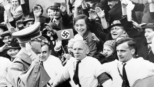 An Associated Press photograph shows Adolf Hitler, German Reichsfuehrer, acknowledging the ecstatic cheers of Sudeten Germans, as he entered Asch, on the heels of German armies which took over the ceded Czechoslovakian territory, on Oct. 3, 1938. The AP caption notes: 'Party members grip each other's belt, straining to hold the enthusiastic crowds in check.'