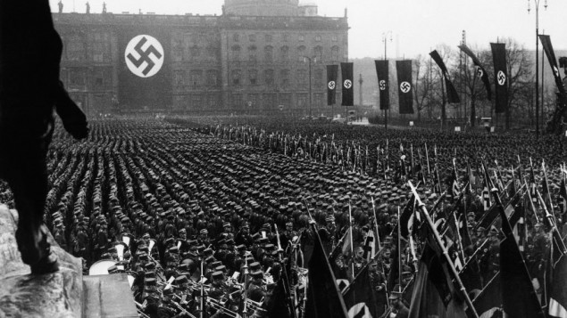The Associated Press photographs the third anniversary of National Socialism's accession to power in 1933 widely celebrated throughout Germany on Feb. 11, 1936. At noon, Adolf Hitler assembled 25,000 of his oldest stormtroop comrades in the Lustgarten in Berlin. In his address, Hitler reiterated Germany's will to peace. This is a general view of the banner and flag bearers in Berlin.