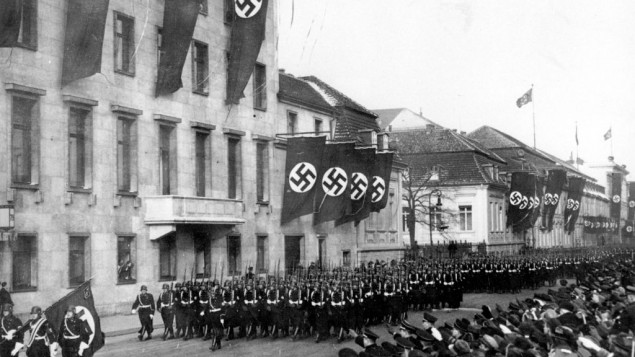 An Associated Press photograph shows a parade of Nazi black guards marching past the Reich Chancellory on Wilhelmstrasse during their parade in Berlin, Germany, on Jan. 30, 1937.