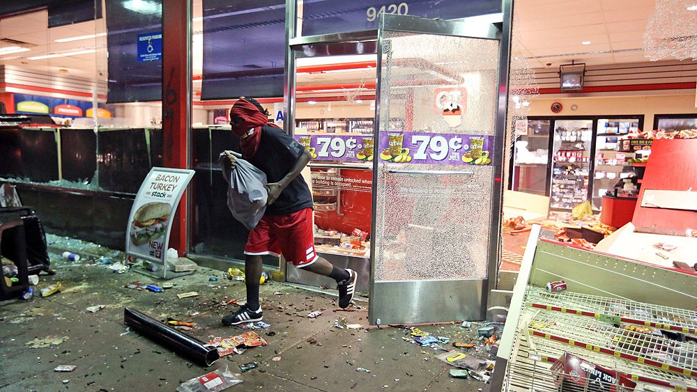 "A young man loots a store on Sunday, Aug. 10, 2014, in Ferguson, Mo. Is he another young thug, or merely a ""justice-involved youth,"" as the U.S. Justice Department would say?"