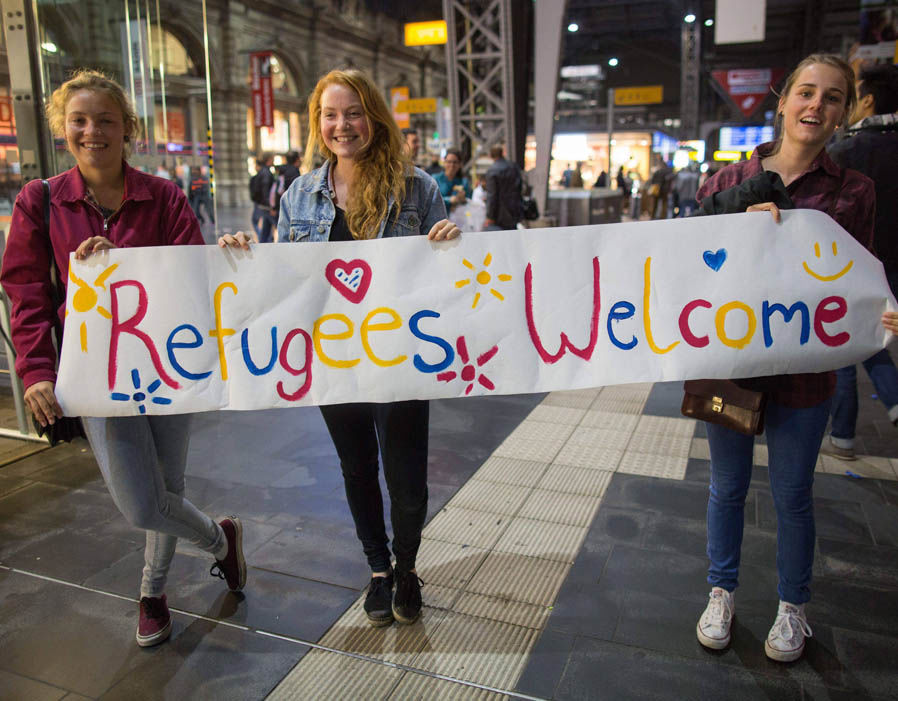women_refugees_welcome_sign