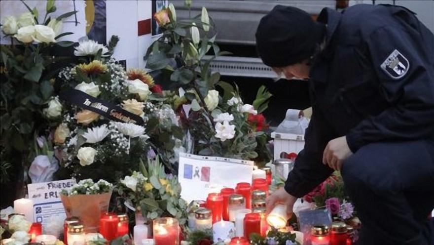 שוטר מדליק נר זיכרון במקום בו ביצע מהגר מוסלמי פיגוע בערב חג המולד 2016 בברלין